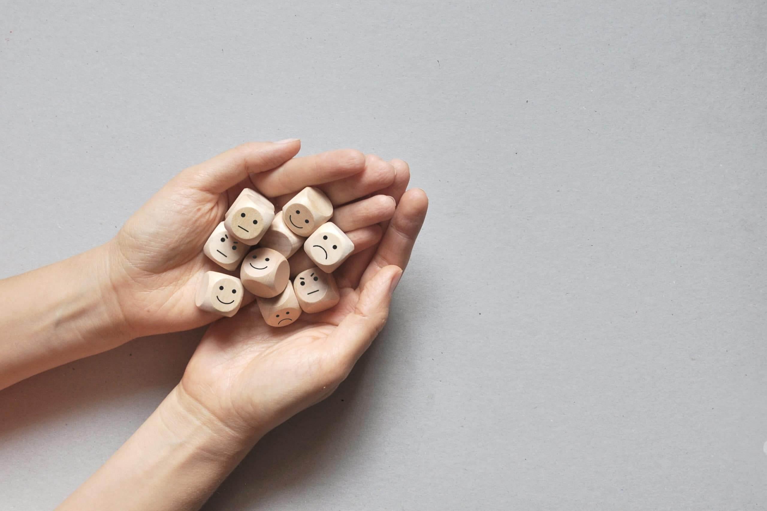 Image of emotions on wooden blocks. Joy, calm, sadness, anger.