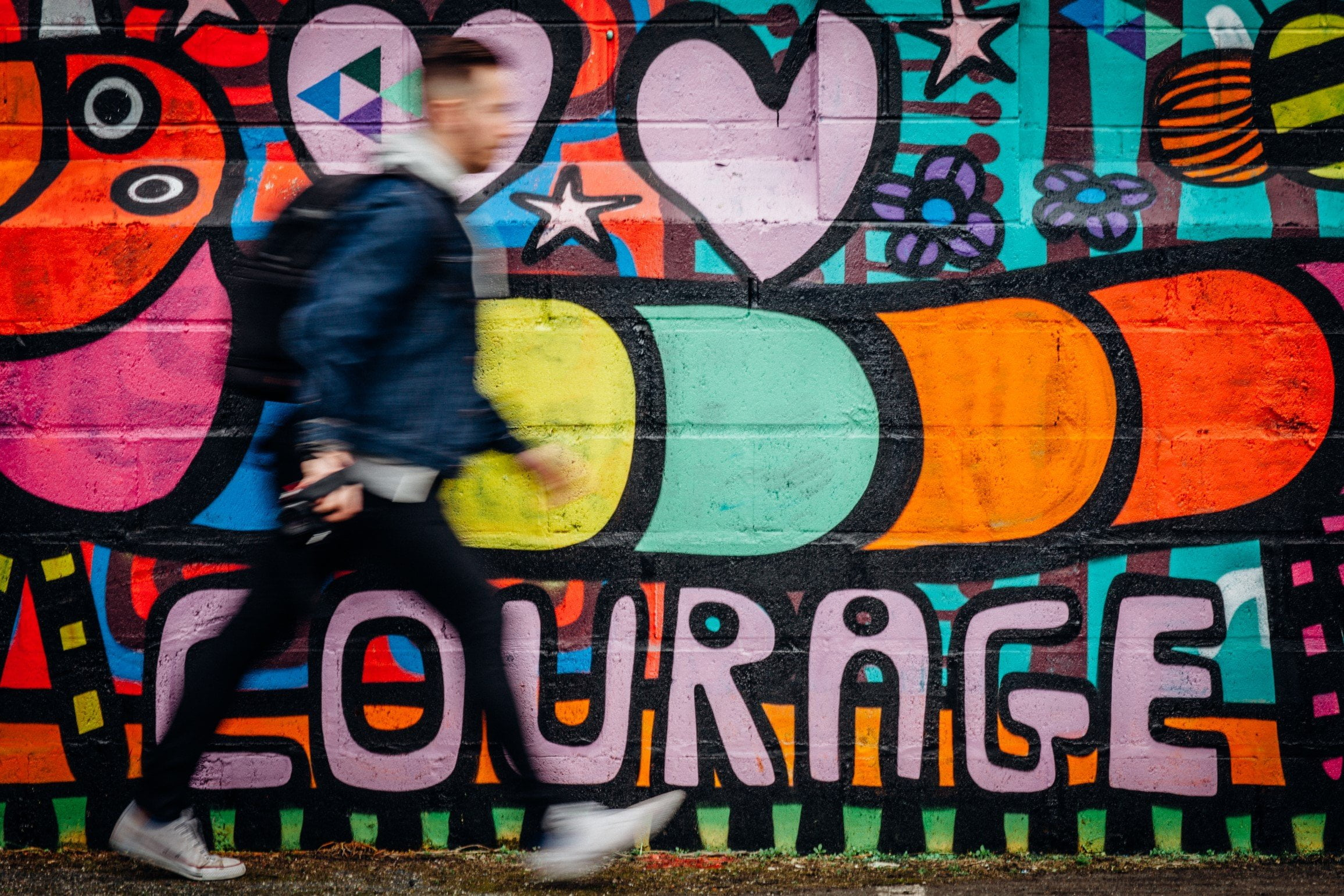 Man walking in front of graffiti that says courage